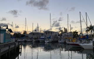 Boats in front of Florida homes during sunset.
